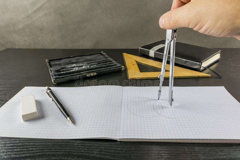 Dibujo de un círculo usando un compás en un talonario de cheques fotografía de archivo
