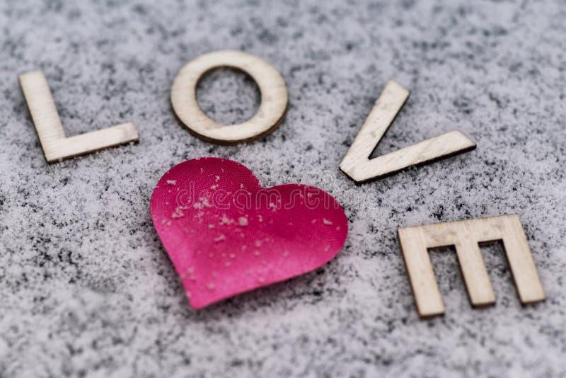 Dibujo de un corazón en el nevoso Día del `s de la tarjeta del día de San Valentín Corazón del rosa en la nieve con las letras du imagenes de archivo