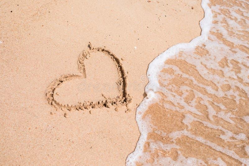 Dibujo de un corazón en una arena amarilla en un fondo hermoso del paisaje marino foto de archivo