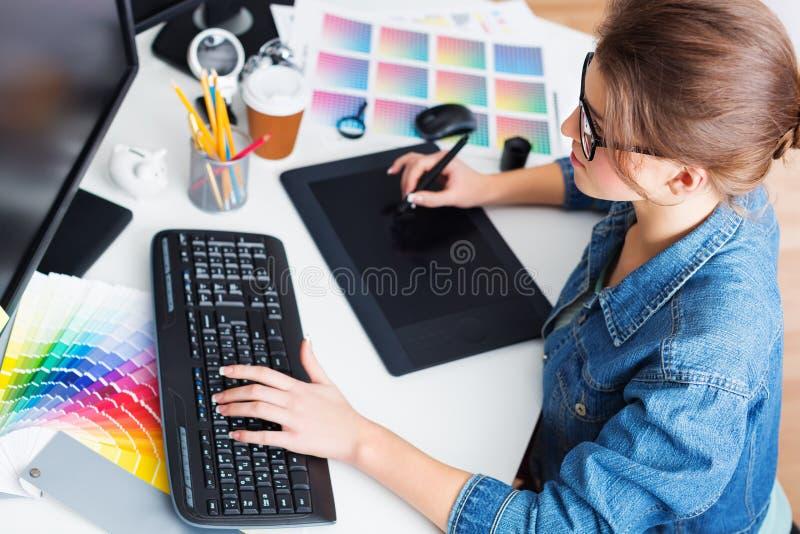 Dibujo del artista algo en la tableta gráfica en imagen de archivo