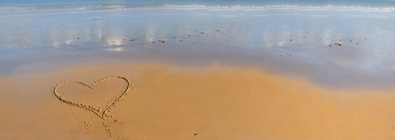 Dibujo del coraz?n en la arena delante del mar fotos de archivo