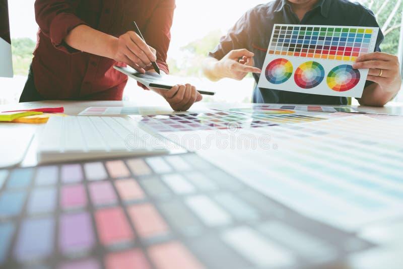Dibujo del diseñador gráfico dos en la tableta de gráficos y el palett del color imagen de archivo