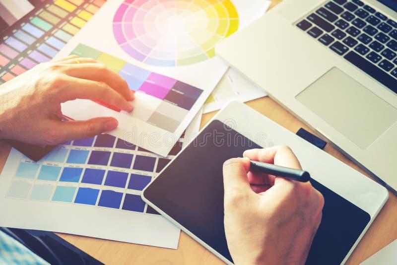 Dibujo del diseñador gráfico en la tableta de gráficos en el lugar de trabajo imagenes de archivo