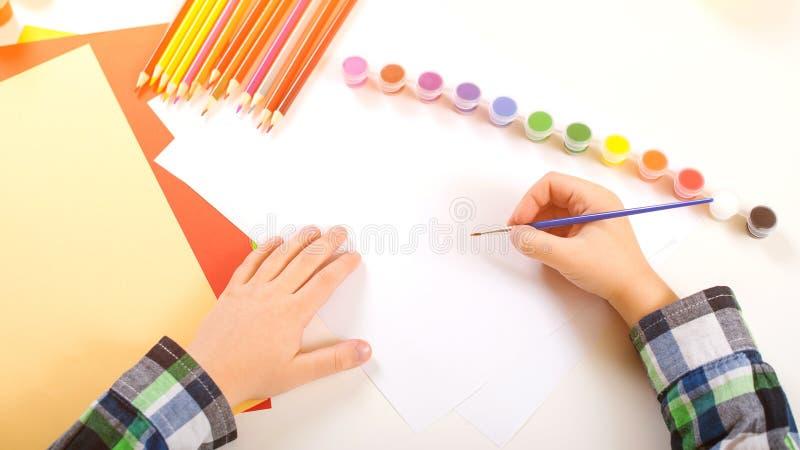 Dibujo del ni?o con las pinturas del color Vista superior de las manos del ni?o con el cepillo Imagen de pintura en el papel De n foto de archivo libre de regalías