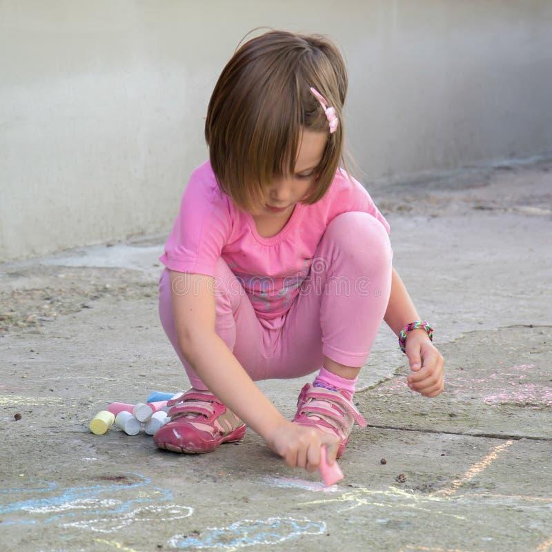 Dibujo del niño con tiza en el asfalto fotos de archivo