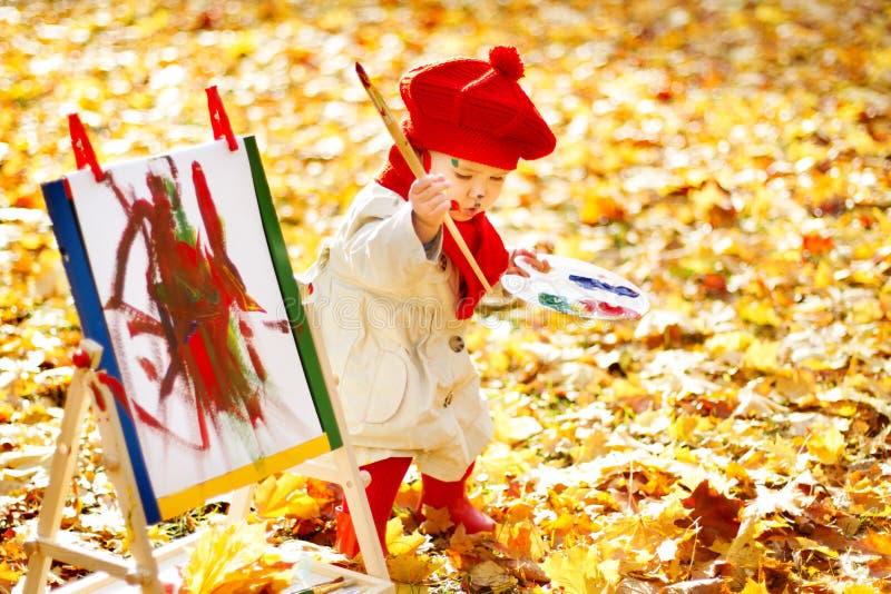 Dibujo del niño en el caballete en Autumn Park. Desarrollo creativo de los niños imagen de archivo