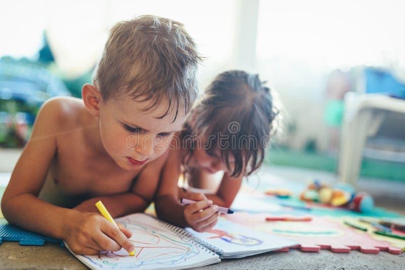 Dibujo del niño pequeño y de la muchacha con los creyones fotos de archivo