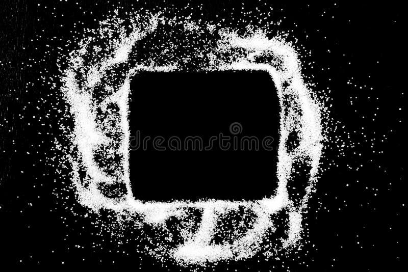 Dibujo del símbolo de la caja de comprobación por el finger en el polvo blanco de la sal en fondo negro imagen de archivo libre de regalías