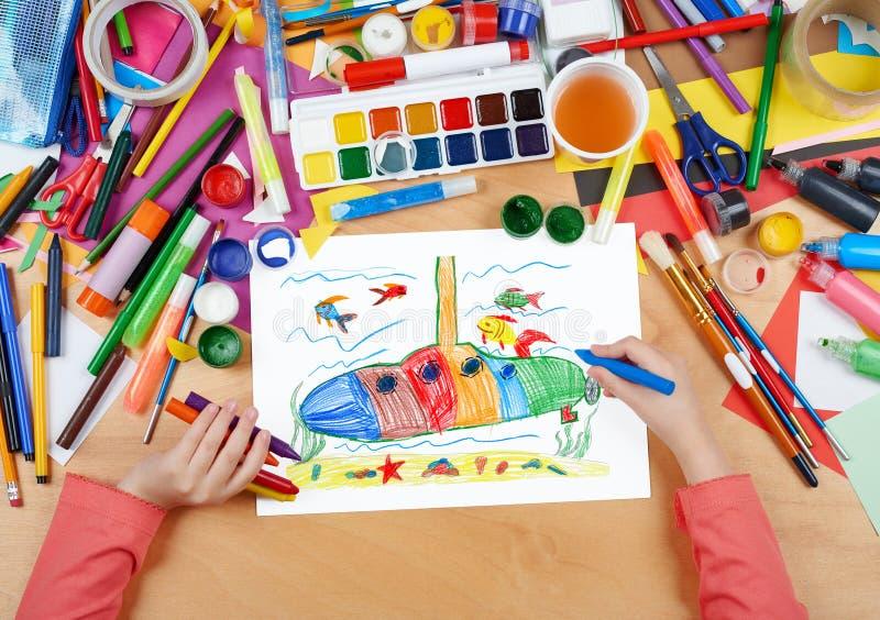 Dibujo del submarino y del niño de la vida marina, manos de la visión superior con la imagen de la pintura del lápiz en el papel, libre illustration