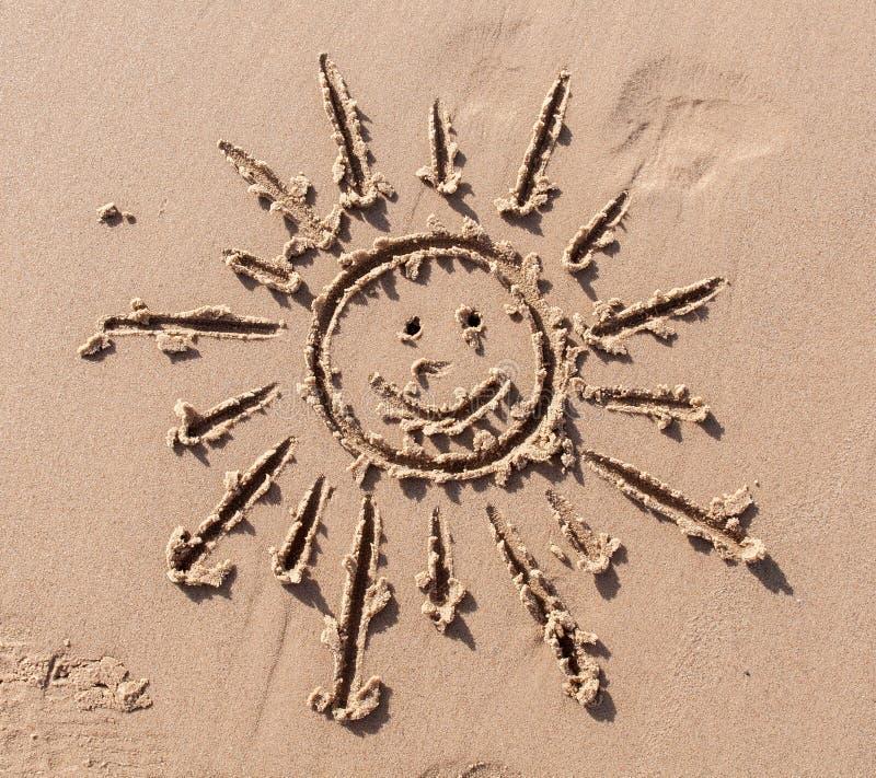 Dibujo divertido del sol y de la sonrisa en la arena de la playa imágenes de archivo libres de regalías
