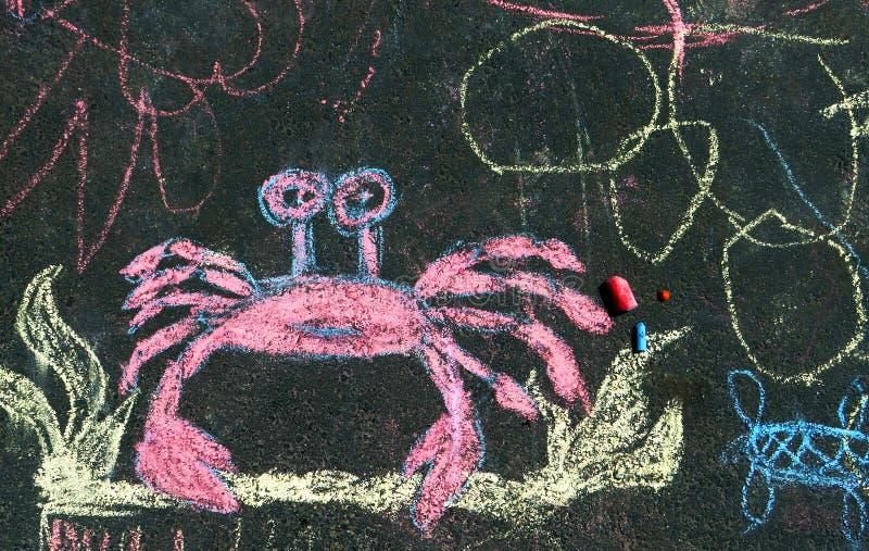 Dibujo en el asfalto con las manos del ` s de los niños fotografía de archivo libre de regalías