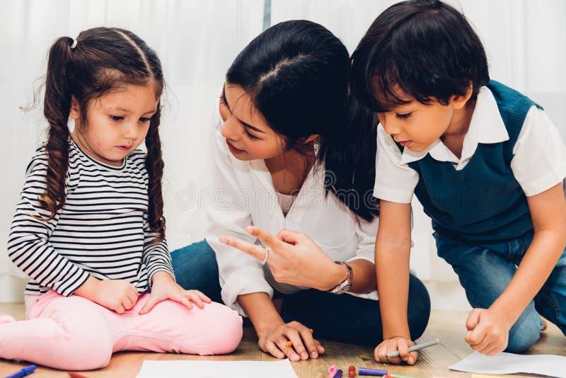 Dibujo feliz de la pintura de la guardería de la muchacha del niño del niño de la familia en peper imagenes de archivo