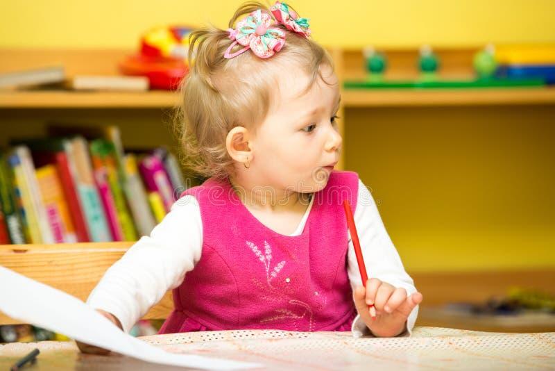 Dibujo lindo de la muchacha del niño con los lápices coloridos en preescolar fotos de archivo