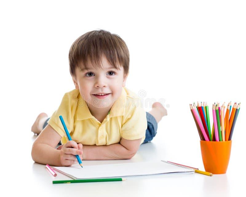 Dibujo lindo del muchacho del niño con los lápices en preescolar fotografía de archivo libre de regalías