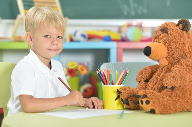 Dibujo lindo del niño pequeño con los lápices en sala de clase imagenes de archivo
