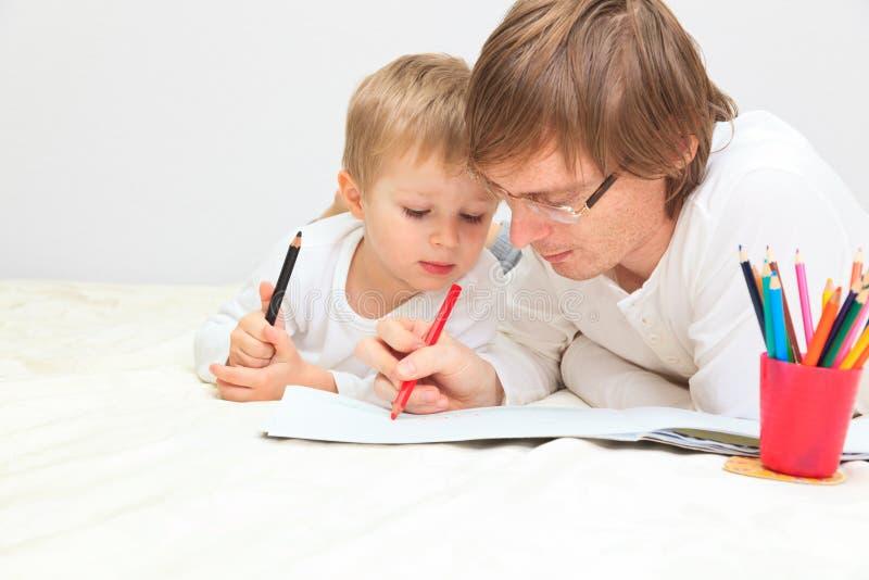 Dibujo o escritura, educación del padre y del hijo imagen de archivo libre de regalías