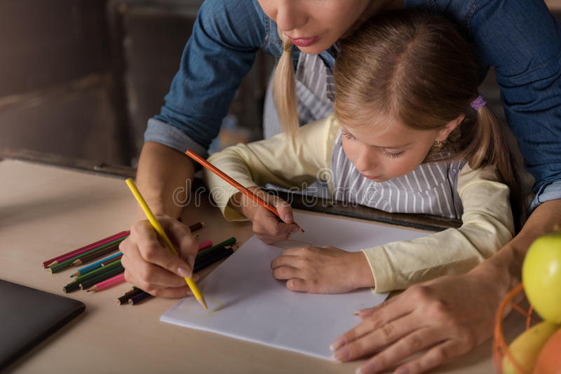 Dibujo precioso de la niña con su madre en la cocina fotos de archivo libres de regalías