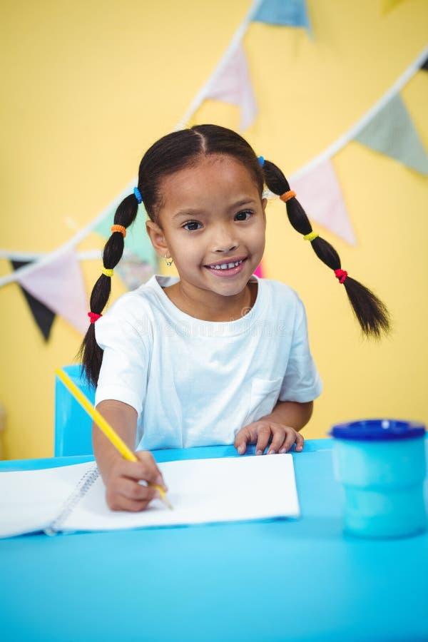 Dibujo sonriente de la muchacha en su libro de colorante imagenes de archivo