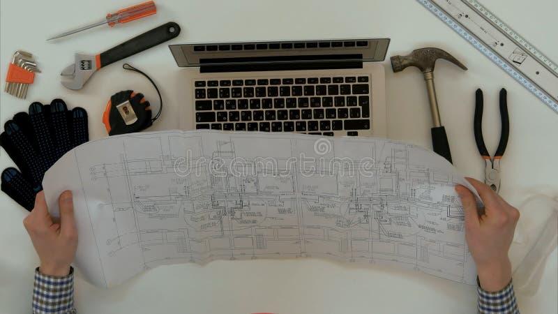 Dibujo técnico de explicación del arquitecto durante la llamada video en el ordenador portátil imagen de archivo