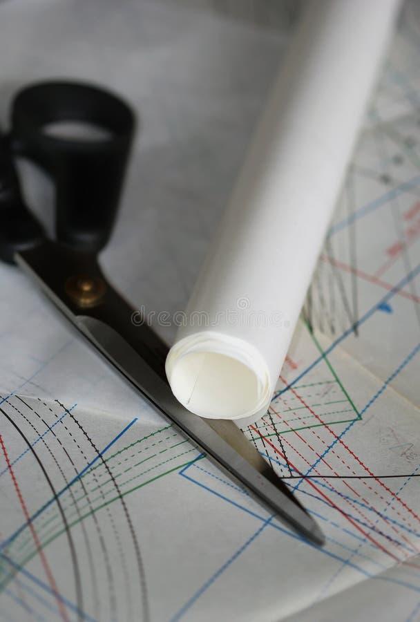 Dibujo, tijeras y rollo de costura del documento de trazo sobre foto de archivo
