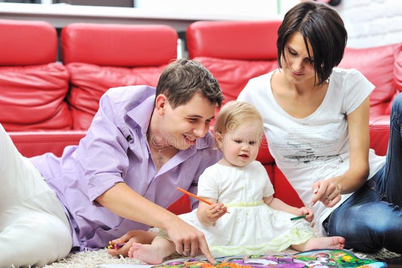 Dibujo y pintura felices de la familia en casa junto imagen de archivo