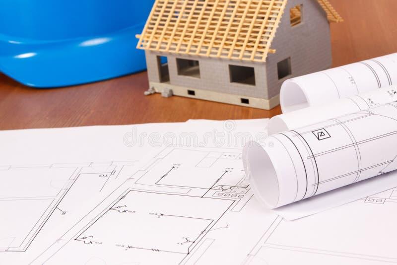 Dibujos eléctricos, casa bajo construcción y casco azul protector, concepto casero constructivo imagen de archivo libre de regalías