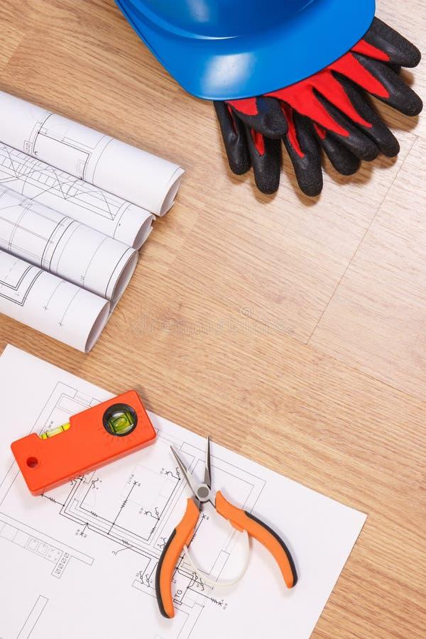 Dibujos o diagramas eléctricos, casco azul protector con los guantes y herramientas anaranjadas del trabajo, concepto de la tecno imagen de archivo