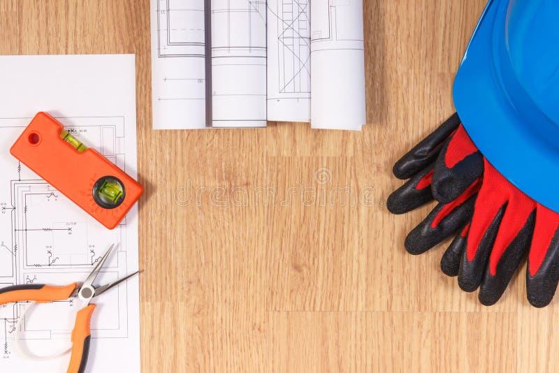 Dibujos o diagramas eléctricos, casco protector con los guantes y herramientas anaranjadas del trabajo imágenes de archivo libres de regalías