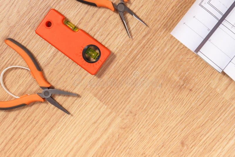 Dibujos o diagramas eléctricos, herramientas anaranjadas del trabajo para el uso en trabajos del ingeniero foto de archivo libre de regalías