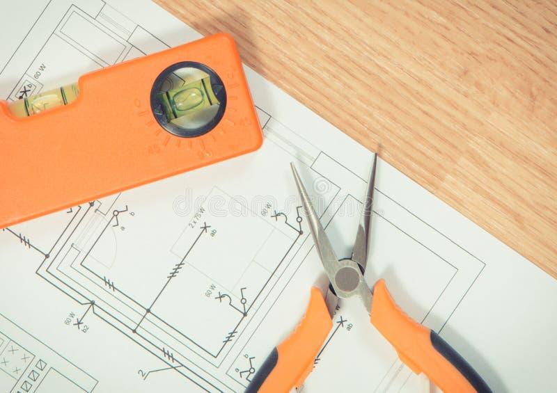 Dibujos o modelos el?ctricos, herramientas anaranjadas del trabajo para el uso en trabajos del ingeniero fotografía de archivo libre de regalías