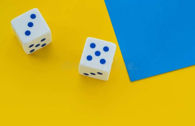 Dice with blue dots on a yellow background royalty free stock image
