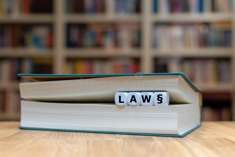 Dice in a book form the word `LAW `. Book is lying on a desk in a library. royalty free stock photography