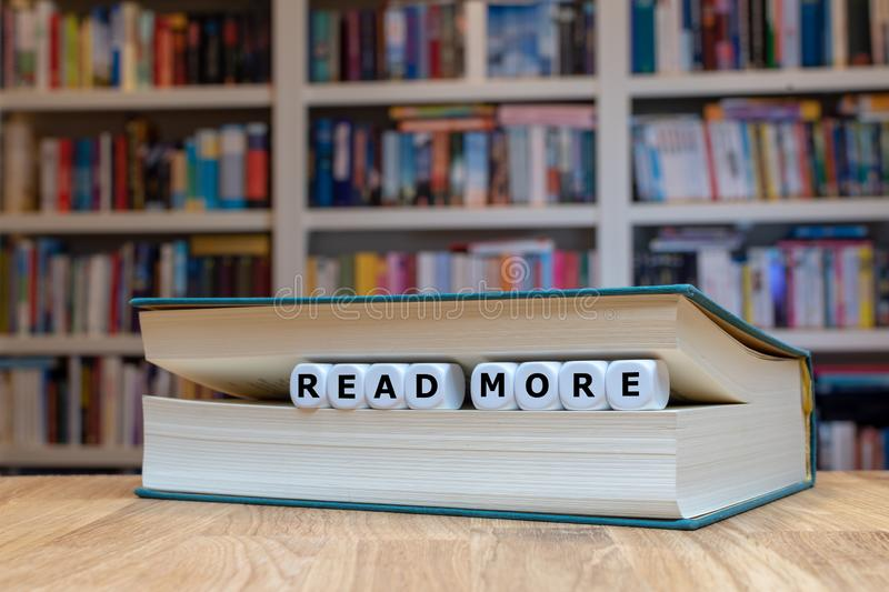 Dice in a book form the words `READ MORE` royalty free stock photo
