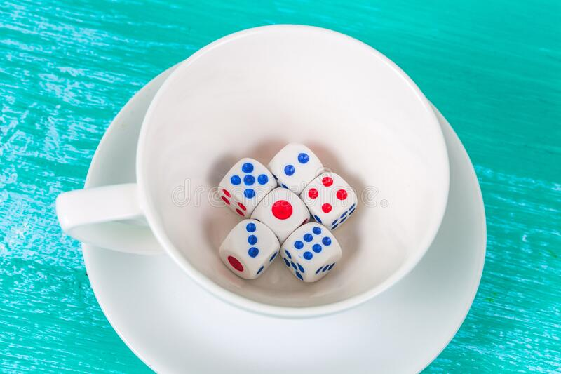Dice in coffee cup on wood. Dice in hite coffee cup on coor wood background stock image