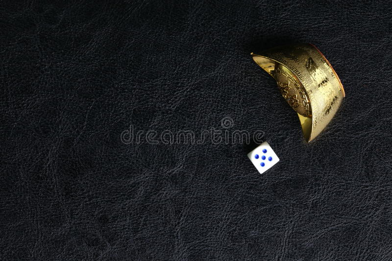 Dice and Chinese gold. Dice and artificial Chinese gold made from plastic represent the symbol of wealth from gambling royalty free stock images
