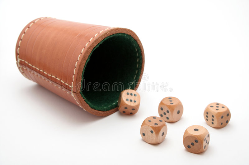 Dice cup. A dice cup and five wooden dice against white background stock photos