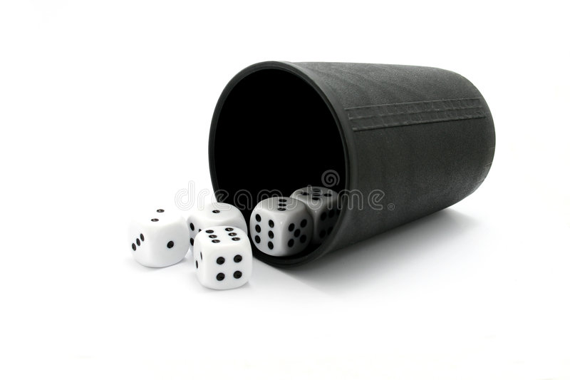 Dice with cup. Five dice with a black dice cup royalty free stock photography