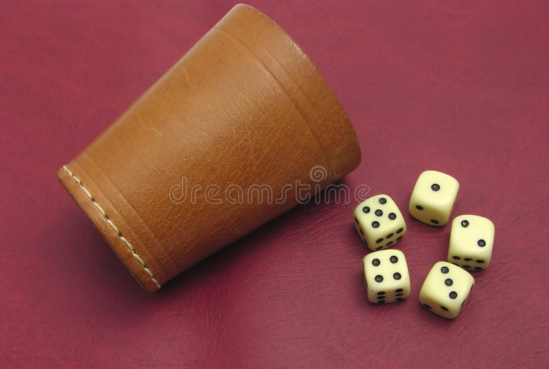Dice cup and dice. On red royalty free stock images