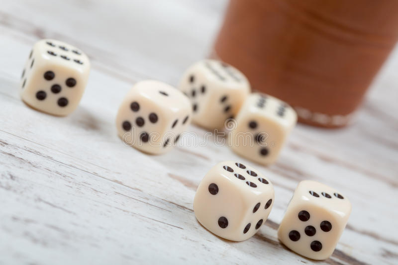 Dice cup and dices. A leather dice cup with several dices stock images