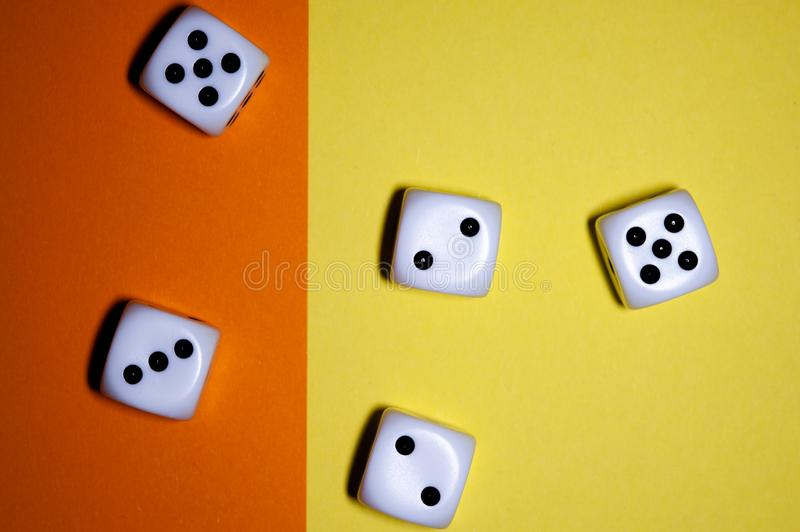 Dice flat lay on Yellow and orange background. Five dice lay flat on a yellow and orange background stock photos