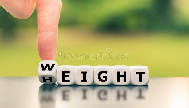 Dice form the words `weight` and `height` stock photo