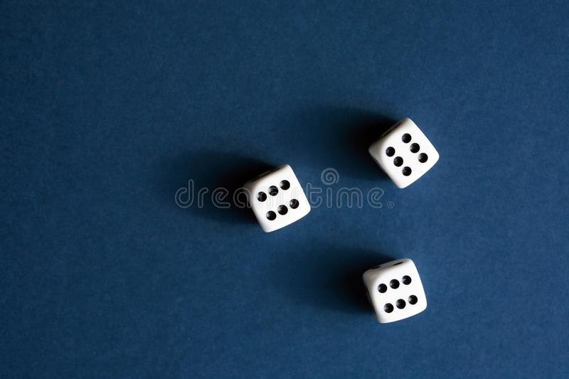 Dice Game On Blue. Three dice cubes on blue background with free space stock photos