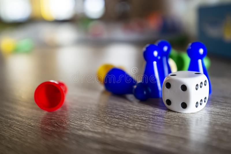 Dice and multi-colored plastic chips from a children`s board game, lie on a wooden table in natural light, on a blurred backgroun royalty free stock photo