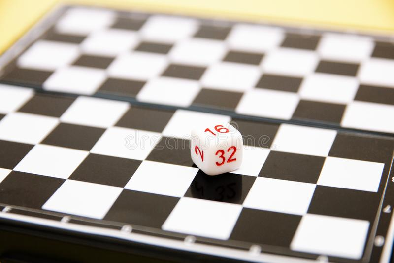 Dice with numbers on the background of the chessboard royalty free stock image