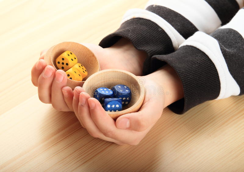 Dice on palms. Yellow and blue dice on palms of hands of little girl stock photography