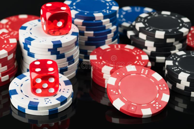 Dice and poker chips on top of black poker table royalty free stock photo