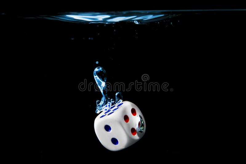 Dice with the number two face in the water with black background royalty free stock photo