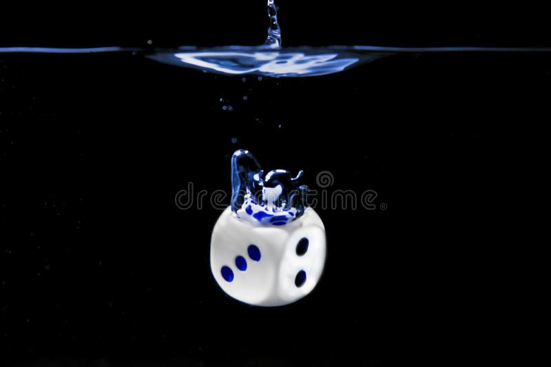Dice with the numbers three and two faces in the water with black background royalty free stock photos