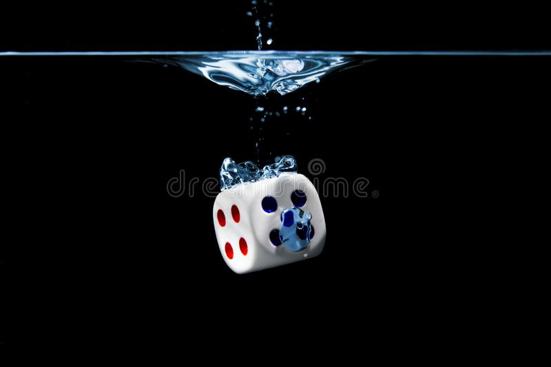 Dice with the numbers four and five faces in the water with black background royalty free stock images