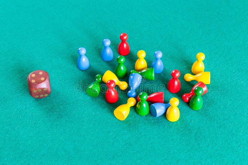 Dice and wooden board game pawns on green table royalty free stock photo